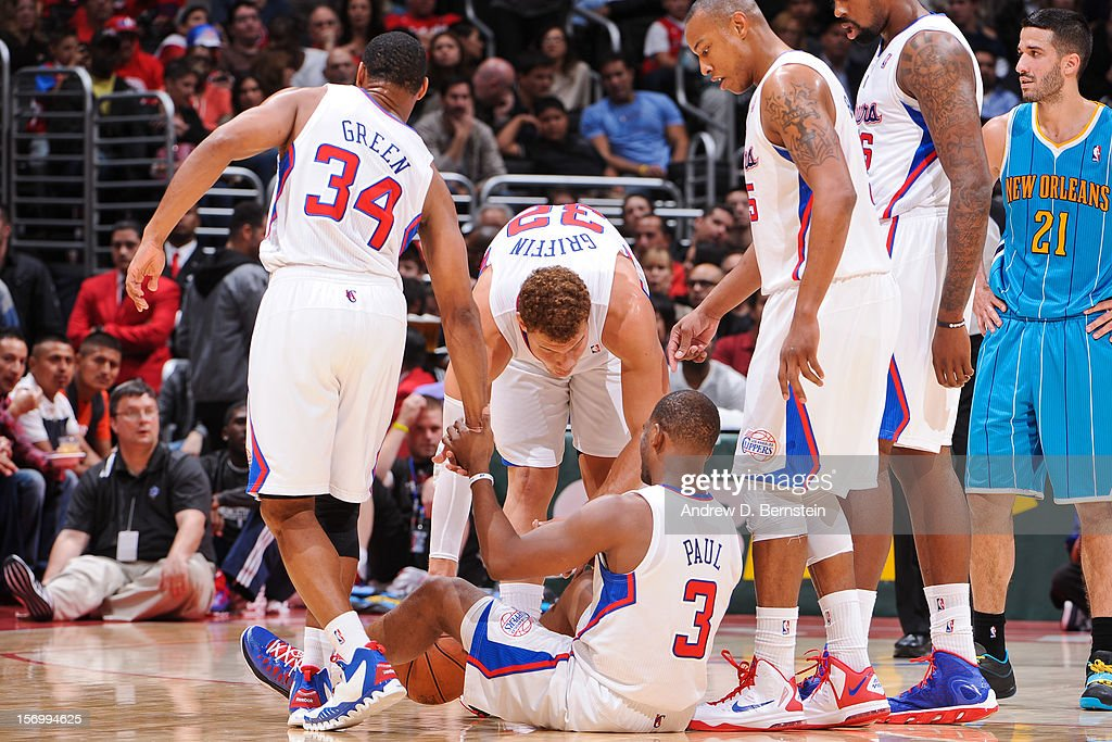 <a gi-track='captionPersonalityLinkClicked' href=/galleries/search?phrase=Chris+Paul&family=editorial&specificpeople=212762 ng-click='$event.stopPropagation()'>Chris Paul</a> #3 of the Los Angeles Clippers is helped up by teammates <a gi-track='captionPersonalityLinkClicked' href=/galleries/search?phrase=Willie+Green&family=editorial&specificpeople=201653 ng-click='$event.stopPropagation()'>Willie Green</a> #34, <a gi-track='captionPersonalityLinkClicked' href=/galleries/search?phrase=Blake+Griffin+-+Basketball+Player&family=editorial&specificpeople=4216010 ng-click='$event.stopPropagation()'>Blake Griffin</a> #32 and <a gi-track='captionPersonalityLinkClicked' href=/galleries/search?phrase=Caron+Butler&family=editorial&specificpeople=201744 ng-click='$event.stopPropagation()'>Caron Butler</a> #5 while playing the New Orleans Hornets at Staples Center on November 26, 2012 in Los Angeles, California.