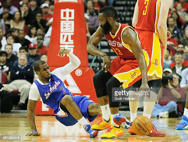 Chris Paul of the Los Angeles Clippers is knocked to the court by James Harden of the Houston Rockets during the game at the Toyota Center on March...