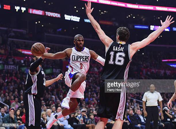 Chris Paul of the Los Angeles Clippers passes between LaMarcus Aldridge and Pau Gasol of the San Antonio Spurs during the game at Staples Center on...
