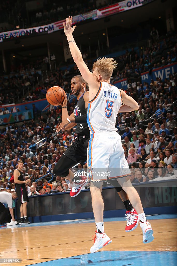 Chris Paul of the Los Angeles Clippers passes the ball against Kyle Singler of the Oklahoma City Thunder on March 9 2016 at Chesapeake Energy Arena...