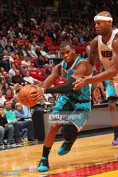 Chris Paul of the New Orleans Hornets drives against Erick Dampier of the Miami Heat on December 13 2010 at American Airlines Arena in Miami Florida...