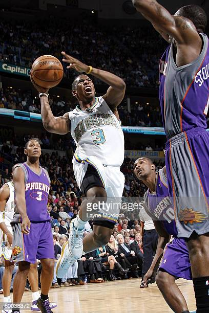 Chris Paul of the New Orleans Hornets goes up for a shot over Leandro Barbosa and Amare Stoudemire of the Phoenix Suns on February 27 2008 at the New...