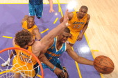 Chris Paul of the New Orleans Hornets has his shot challenged by Pau Gasol of the Los Angeles Lakers in Game Two of the Western Conference...