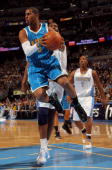 Chris Paul of the New Orleans Hornets looks to pass ahead of Nene of the Denver Nuggets in Game Two of the Western Conference Quarterfinals during...