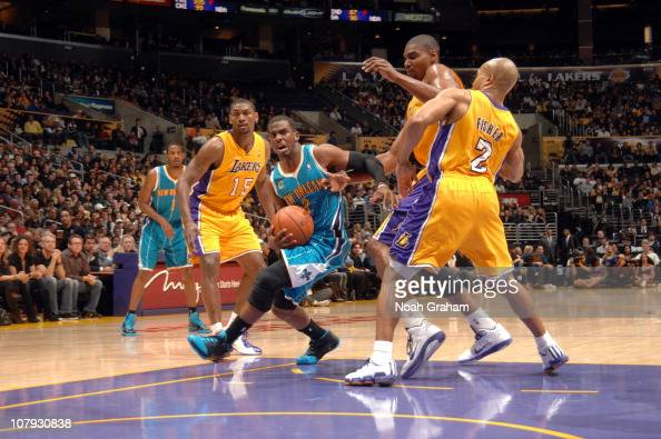 Chris Paul of the New Orleans Hornets makes his way to the basket against Andrew Bynum and Derek Fisher of the Los Angeles Lakers at Staples Center...