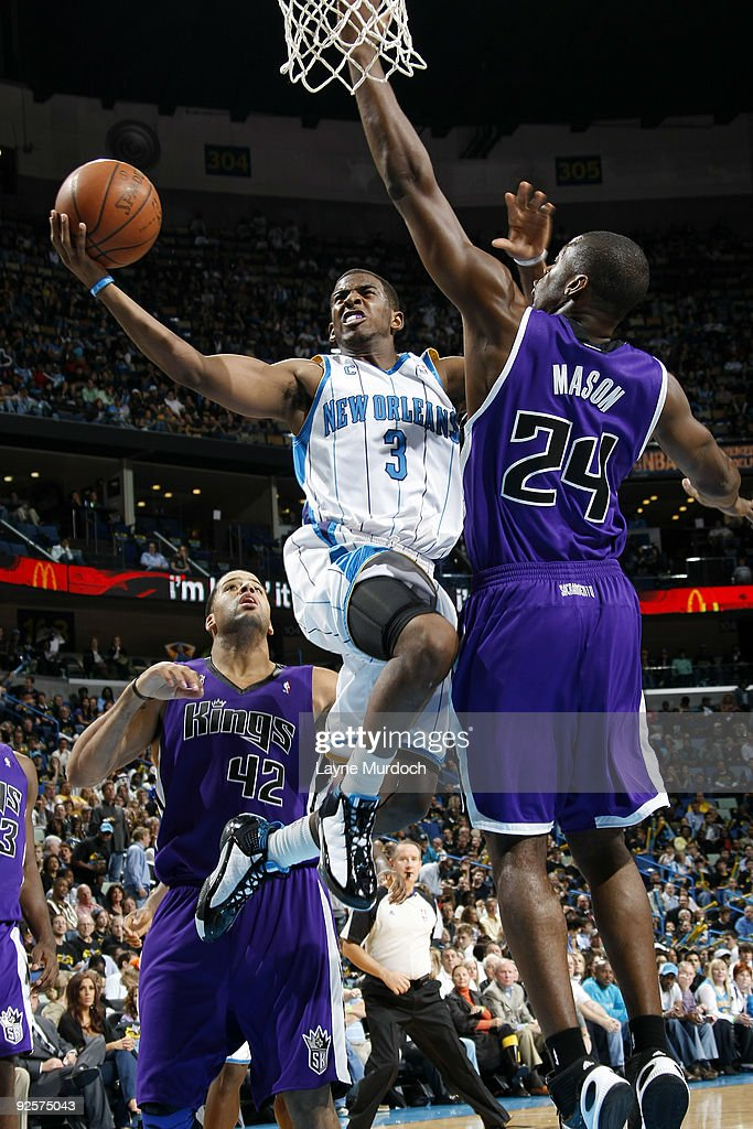 Chris Paul of the New Orleans Hornets shoots over Sean May and Desmond Mason of the Sacramento Kings on October 30 2009 at the New Orleans Arena in...