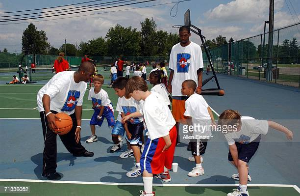 Chris Paul of the New Orleans/Oklahoma City Hornets with an assist from Rip Hamilton of the Detroit Pistons demostrates dribbling skills to campers...