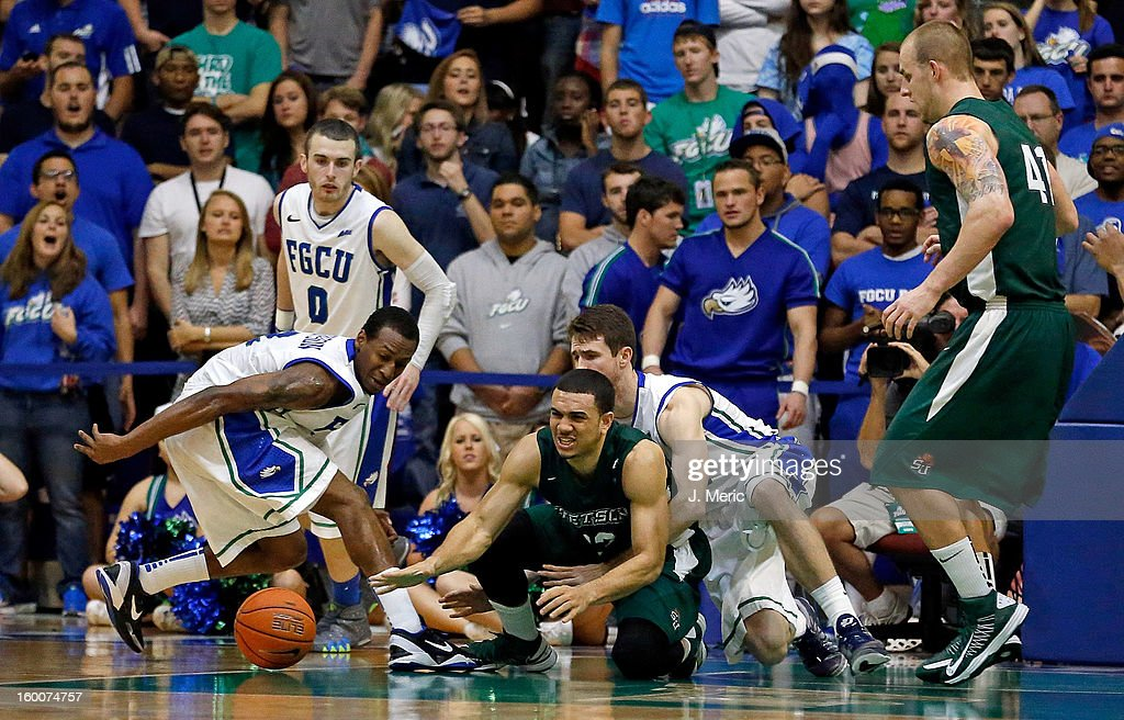 Chris Perez #23 of the Stetson Hatters loses the ball as Bernard Thompson #2 of the Florida Gulf Coast University Eagles dives for the loose ball during the game at Alico Arena on January 25, 2013 in Ft. Myers, Florida.