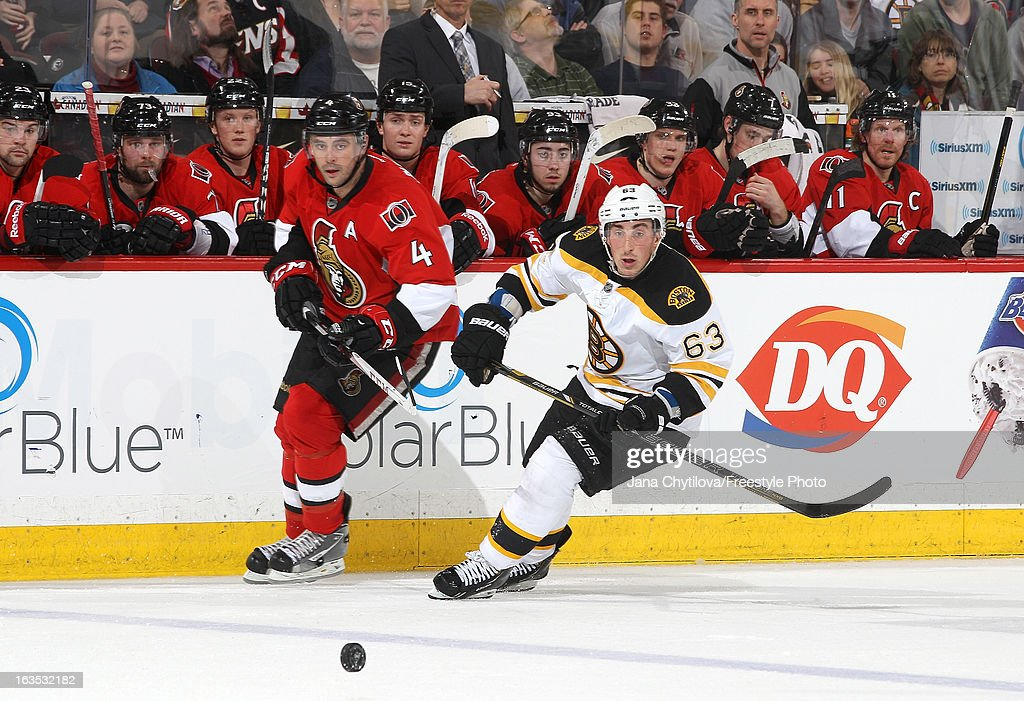 Chris Phillips #4 of the Ottawa Senators and Brad Marchand #63 of the Boston Bruins, skate after the loose puck, during an NHL game at Scotiabank Place, on March 11, 2013 in Ottawa, Ontario, Canada.