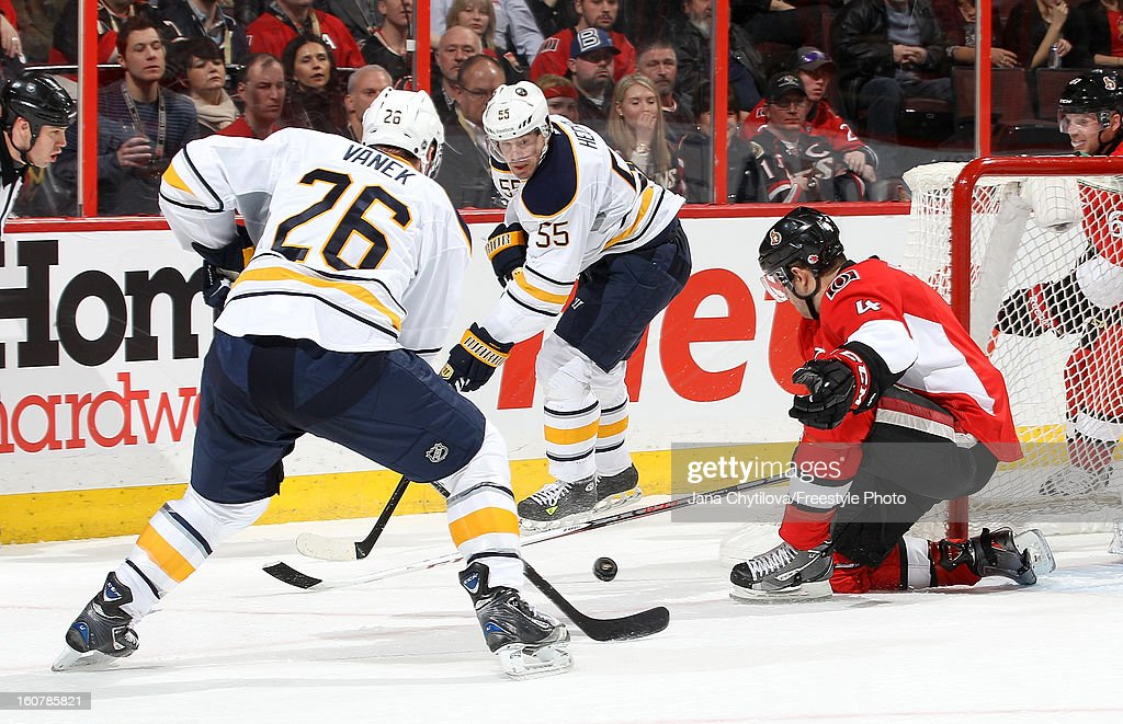 Chris Phillips #4 of the Ottawa Senators blocks a pass from Jochen Hecht #55 of the Buffalo Sabres as Thomas Vanek #26 of the Buffalo Sabres looks on, during an NHL game at Scotiabank Place on February 5, 2013 in Ottawa, Ontario, Canada.