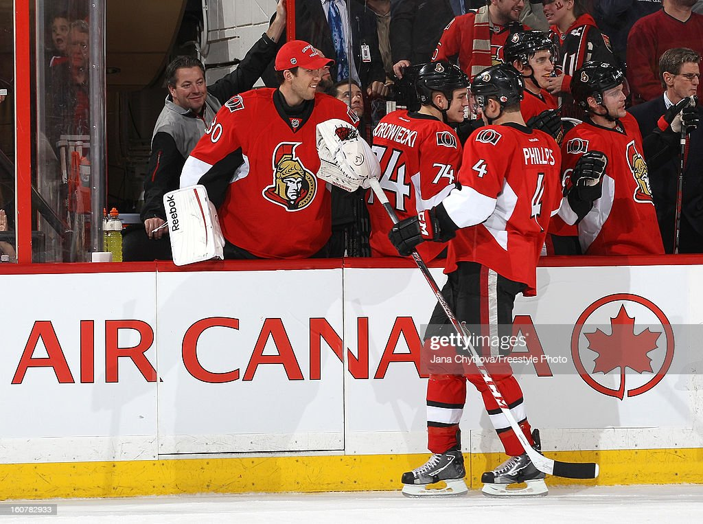 Chris Phillips #4 of the Ottawa Senators celebrates his first period goal with teammates Ben Bishop #30 and Mark Borowiecki #74 during an NHL game against the Buffalo Sabres at Scotiabank Place on February 5, 2013 in Ottawa, Ontario, Canada.