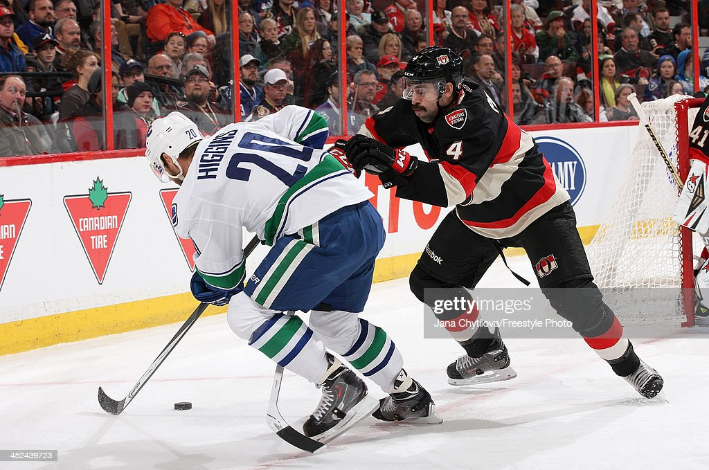Chris Phillips #4 of the Ottawa Senators defends against a puck carrying Chris Higgins #20 of the Vancouver Canucks during an NHL game at Canadian Tire Centre on November 28, 2013 in Ottawa, Ontario, Canada.