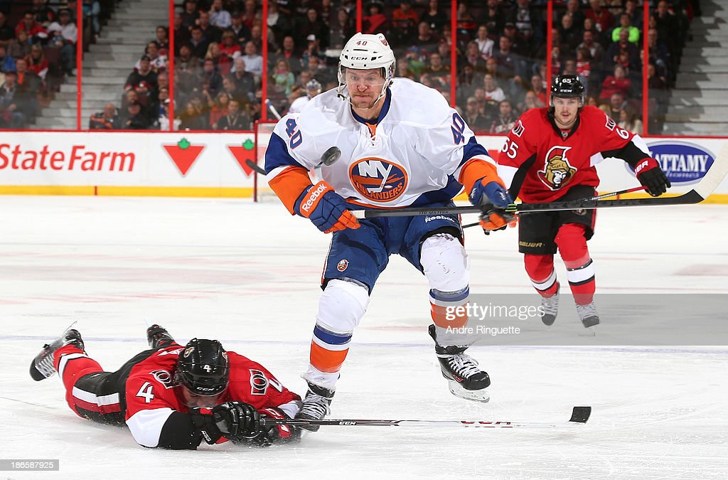 Chris Phillips #4 of the Ottawa Senators dives to chip the puck away as <a gi-track='captionPersonalityLinkClicked' href=/galleries/search?phrase=Michael+Grabner&family=editorial&specificpeople=537955 ng-click='$event.stopPropagation()'>Michael Grabner</a> #40 of the New York Islanders keeps an eye on it at Canadian Tire Centre on November 1, 2013 in Ottawa, Ontario, Canada.