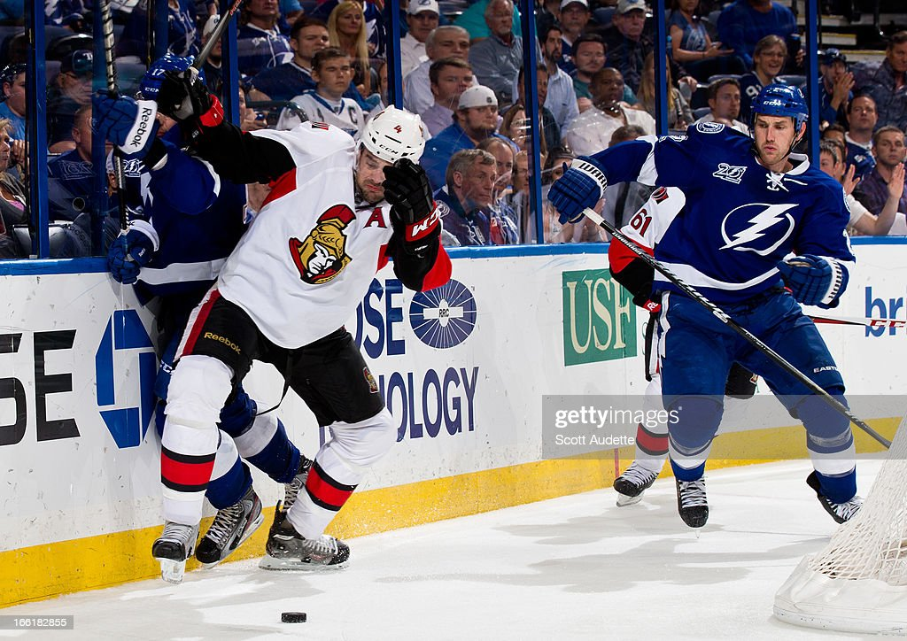 Chris Phillips #4 of the Ottawa Senators fights for control of the puck against the Tampa Bay Lightning during the third period of the game at the Tampa Bay Times Forum on April 9, 2013 in Tampa, Florida.