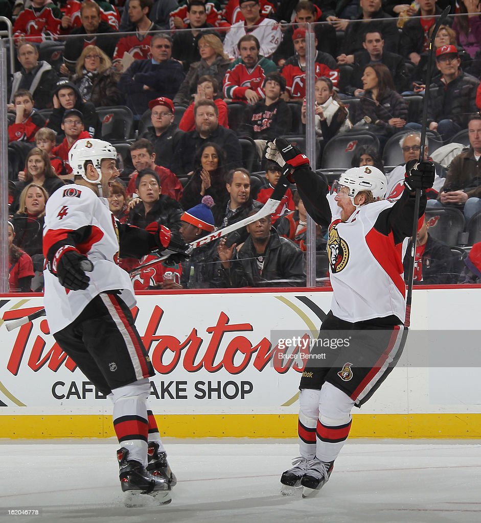 Chris Phillips of the Ottawa Senators greets Daniel Alfredsson following his game tying goal in the third period against the New Jersey Devils at the...