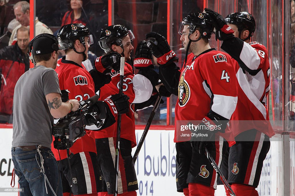 Chris Phillips of the Ottawa Senators highfives teammate Erik Karlsson following their win against the Winnipeg Jets during an NHL game at Canadian...