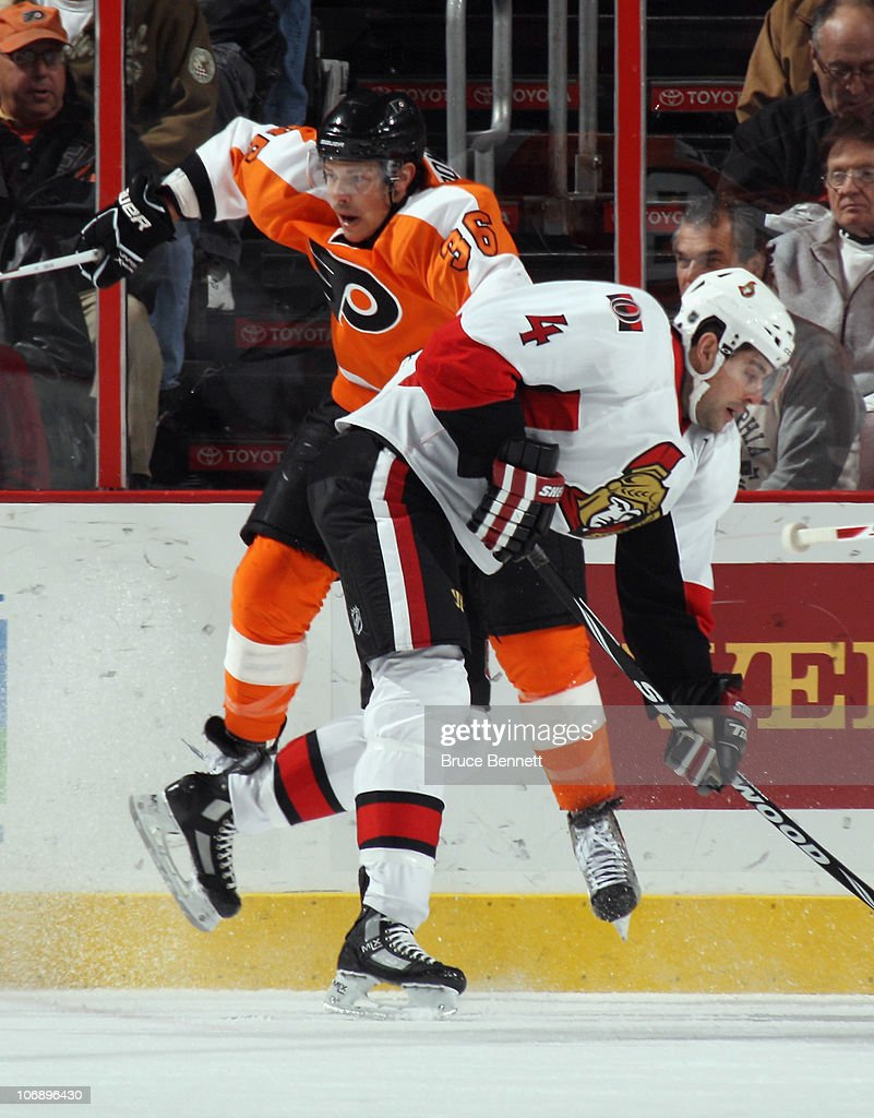 Chris Phillips #4 of the Ottawa Senators hits Darroll Powe #36 of the Philadelphia Flyers at the Wells Fargo Center on November 15, 2010 in Philadelphia, Pennsylvania.