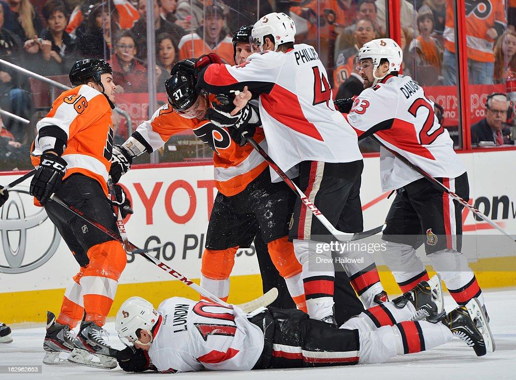 Chris Phillips #4 of the Ottawa Senators hits Harry Zolnierczyk #37 of the Philadelphia Flyers after a check on Mike Lundin #10 of the Senators at the Wells Fargo Center on March 2, 2013 in Philadelphia, Pennsylvania.