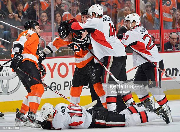 Chris Phillips of the Ottawa Senators hits Harry Zolnierczyk of the Philadelphia Flyers after a check on Mike Lundin of the Senators at the Wells...
