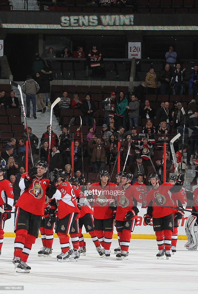 Chris Phillips #4 of the Ottawa Senators raises his stick to salute the fans along with teammates after their win over the Buffalo Sabres on February 5, 2013 at Scotiabank Place in Ottawa, Ontario, Canada.