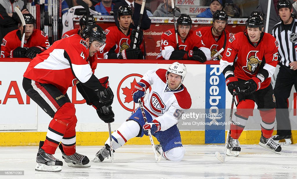 Chris Phillips #4 of the Ottawa Senators reacts as <a gi-track='captionPersonalityLinkClicked' href=/galleries/search?phrase=David+Desharnais&family=editorial&specificpeople=4084305 ng-click='$event.stopPropagation()'>David Desharnais</a> #51 of the Montreal Canadiens makes a pass while down on one knee, during an NHL game at Scotiabank Place on February 25, 2013 in Ottawa, Ontario, Canada.