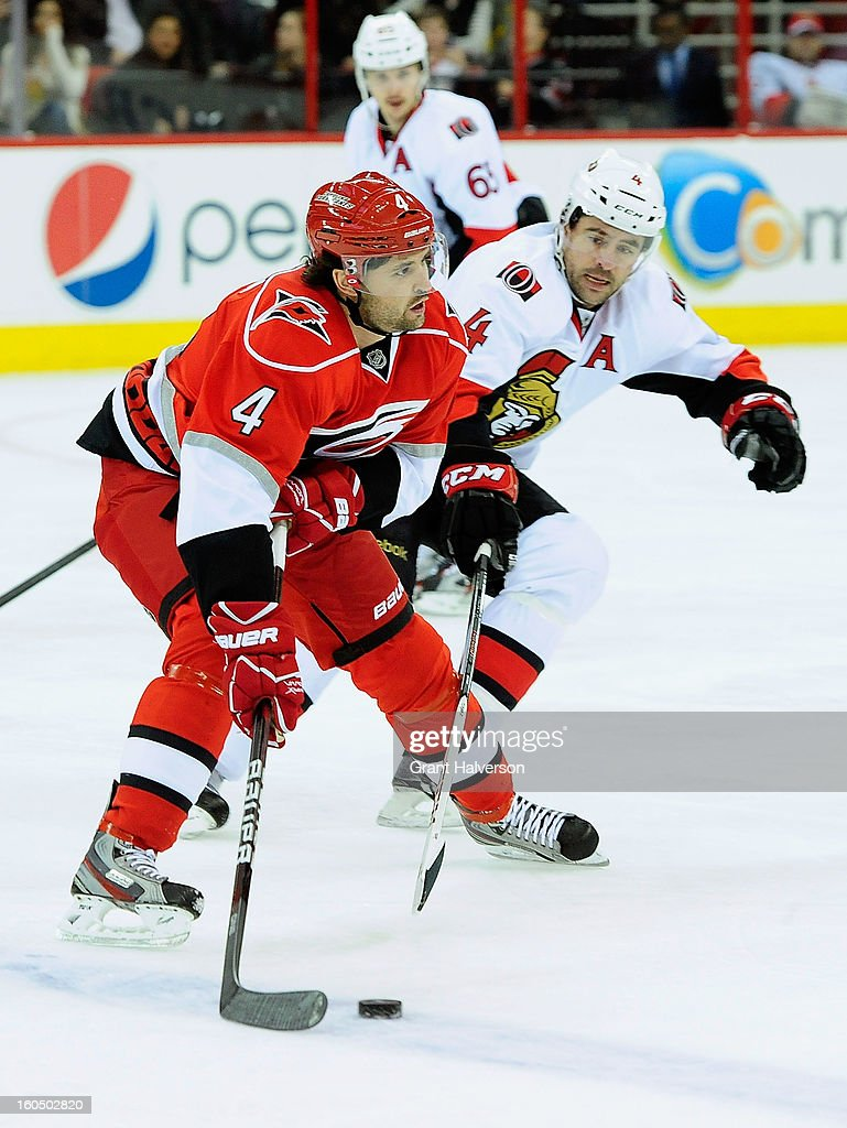 Chris Phillips #4 of the Ottowa Senators defends against Jamie McBain #4 of the Carolina Hurricanes during play at PNC Arena on February 1, 2013 in Raleigh, North Carolina.