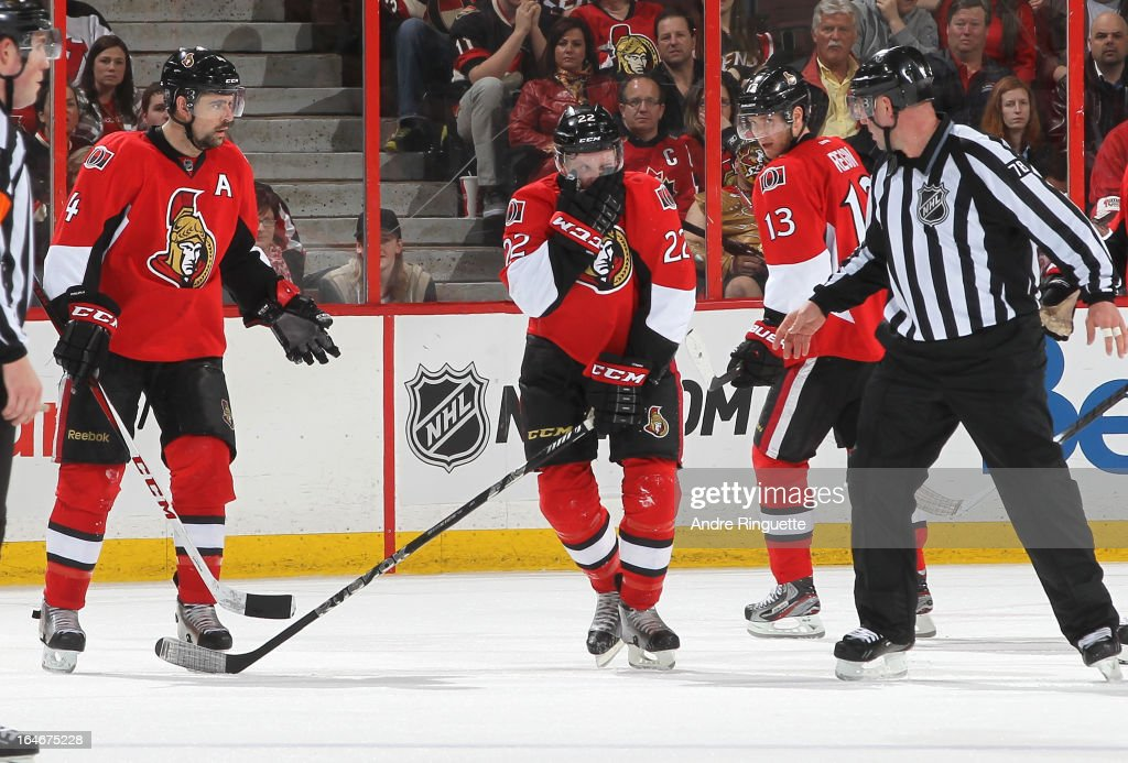 Chris Phillips #4, Peter Regin #13 of the Ottawa Senators and linesman Brian Mach look on as Erik Condra #22 covers his face after being hit with the puck during an NHL game against the New Jersey Devils on March 25, 2013 at Scotiabank Place in Ottawa, Ontario, Canada.