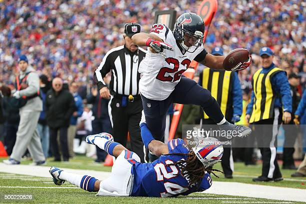 Chris Polk of the Houston Texans hurdles over Stephon Gilmore of the Buffalo Bills for a touchdown during the first half at Ralph Wilson Stadium on...