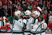 Chris Porter and David Jones of the Minnesota Wild celebrate with teammates after defeating the Chicago Blackhawks 3 to 2 in a shootout during the...