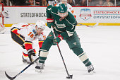 Chris Porter of the Minnesota Wild handles the puck with Josh Jooris of the Calgary Flames defending during the game on April 9 2016 at the Xcel...