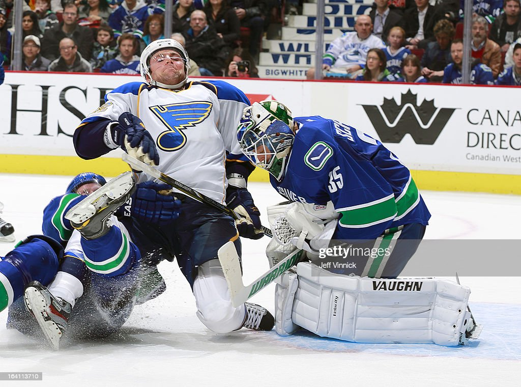 Chris Porter #32 of the St. Louis Blues is held in check while <a gi-track='captionPersonalityLinkClicked' href=/galleries/search?phrase=Cory+Schneider&family=editorial&specificpeople=696908 ng-click='$event.stopPropagation()'>Cory Schneider</a> #35 of the Vancouver Canucks makes a save during their NHL game at Rogers Arena March 19, 2013 in Vancouver, British Columbia, Canada. Vancouver won 3-2.