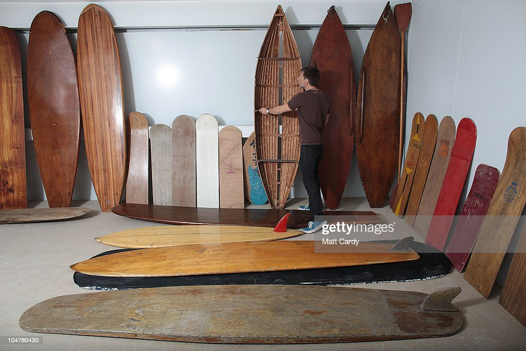 Chris Preston holds a early wooden surfboard as he stands amongst part of the Museum of British Surfing surfboard collection, the largest in the UK and currently in storage, on October 4, 2010 in Braunton, England. The Museum of British Surfing, a charity which originally started online, has been touring the UK since 2004 and is Europe's first surf museum. It holds the largest surfboard collection in Britain and has secured funding for a permanent home, which will open in Braunton next summer. As well as the collection of surfboards dating back over 100 years, the museum also holds early wetsuits, photos and other memorabilia relating to the phenomenal growth in the popularity of surfing. Although many people assume surfing in the UK began in the 1960s, the museum contains evidence that show that it was in fact already a mass participant activity on British beaches by the end of the First World War. Surfing is now a multi-million pound industry and employs 1000s of people in the UK.