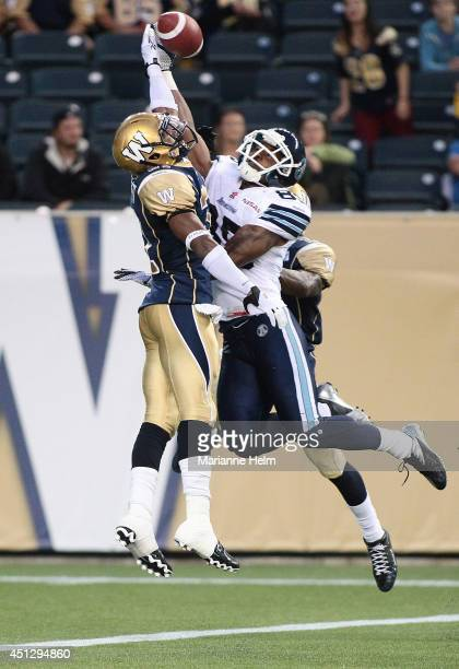 Chris Randle and Maurice Leggett of the Winnipeg Blue Bombers put pressure on John Chiles of the Toronto Argonauts in second half action in a CFL...