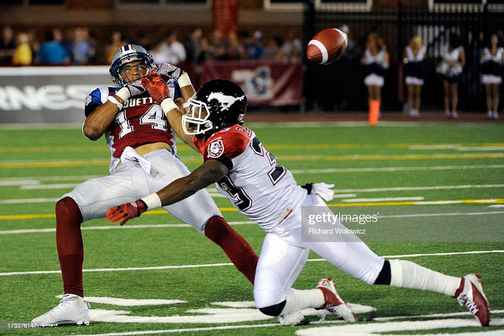Chris Randle #33 of the Calgary Stampeders blocks Brandon London #14 of the Montreal Alouettes from catching the ball during the CFL game at Percival Molson Stadium on July 12, 2013 in Montreal, Quebec, Canada. The Stampeders defeated the Alouettes 22-14.