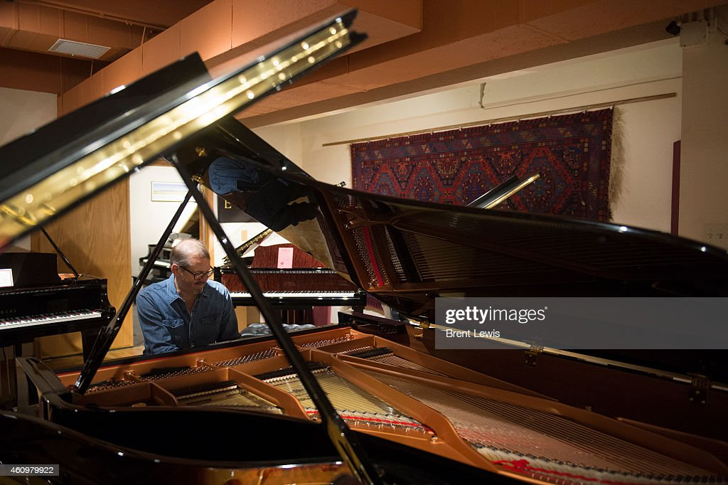 Chris Ranney tests out a piano that was just tuned by Gary Bondurant on Friday January 2 2015 at Onofrio Piano Company in Denver Colorado Onofrio has...