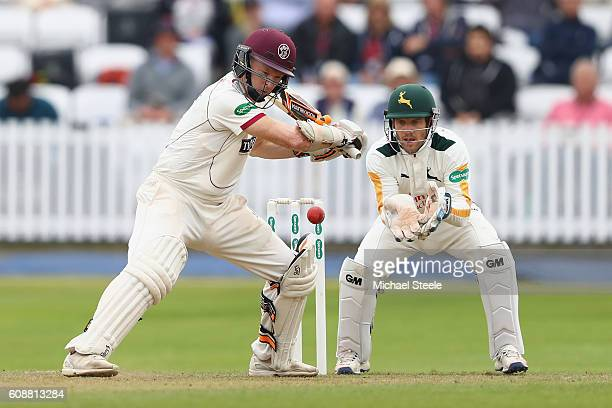 Chris Rogers of Somerset cuts a delivery from Matthew Carter as wicketkeeper Chris Read looks on during day one of the Specsavers County Championship...