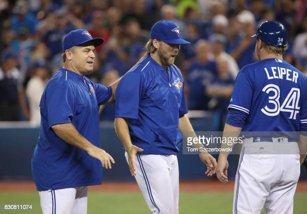 Chris Rowley of the Toronto Blue Jays is congratulated by manager John Gibbons after recording his first MLB victory during MLB game action against...