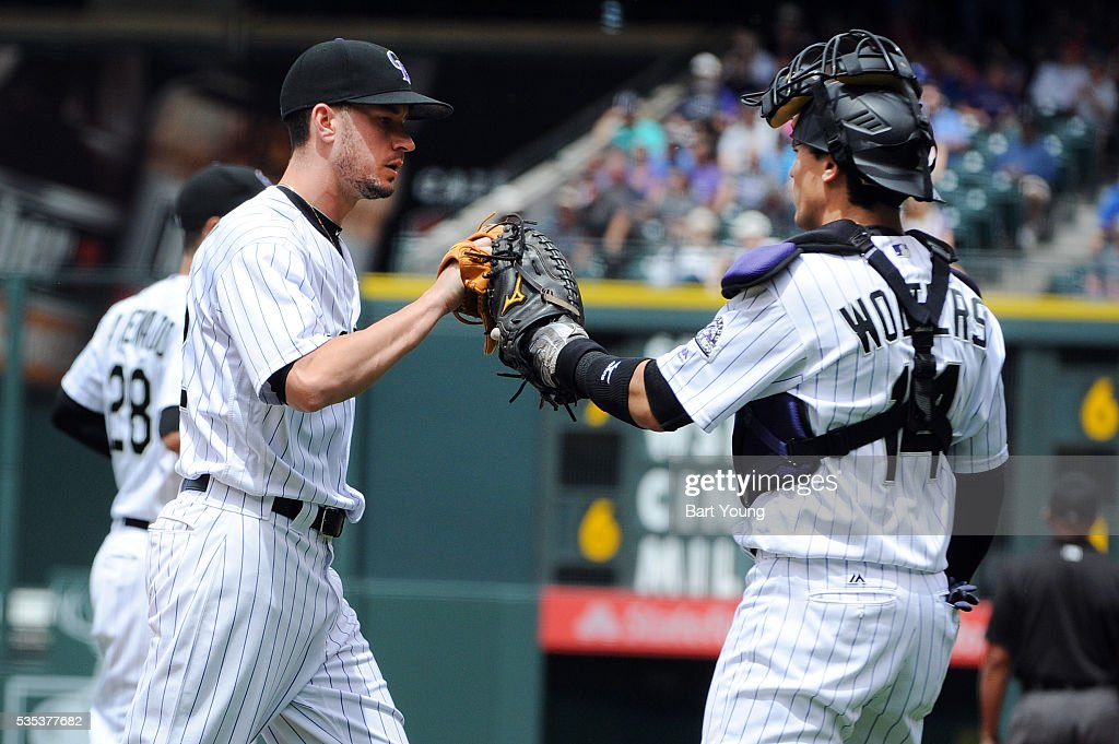 Chris Rusin #52 and Tony Wolters #14 of the Colorado Rockies react to a play against the San Francisco Giants at Coors Field on May 29, 2016 in Denver, Colorado.