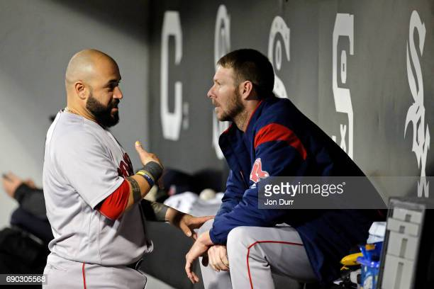 Chris Sale of the Boston Red Sox and Sandy Leon talk in the dugout during the top of the third inning of their game against the Chicago White Sox at...