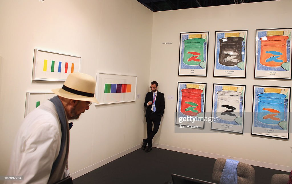 Chris Santa Maria leans against a wall with art hanging on it at the Gemini GEL gallery as Art Basel opens at the Miami Beach Convention Center on December 5, 2012 in Miami Beach, Florida. The 11th edition of the art show runs from December 6 through the 9th.
