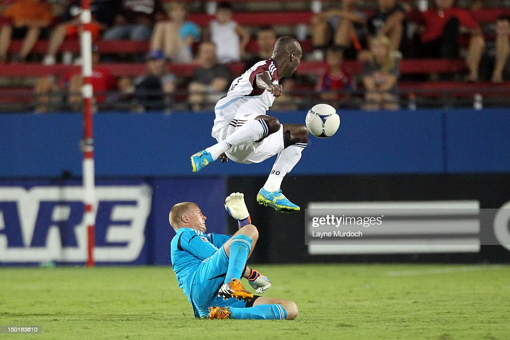 Chris Seitz goal keeper for FC Dallas slides under Omar Cummings of the Colorado Rapids at FC Dallas Stadium on August 11 2012 in Frisco Texas