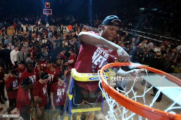 Chris Silva of the South Carolina Gamecocks celebrates by cutting down the net after defeating the Florida Gators with a score of 77 to 70 to win the...