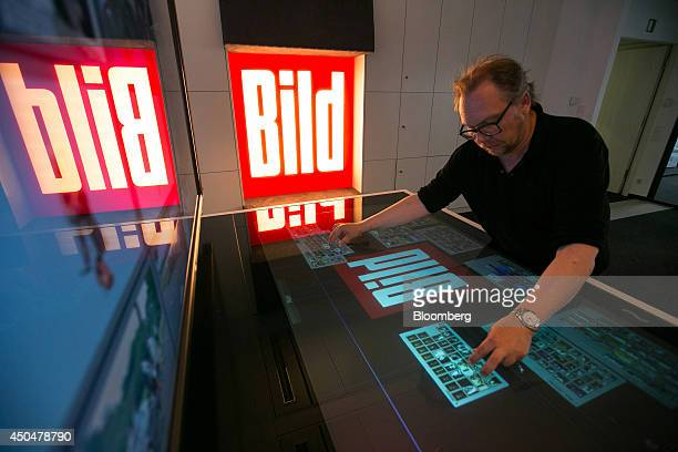 Chris Simon managing editor of Bild a tabloid newspaper uses a touch screen panel as he edits images on the digital photo desk inside the offices of...