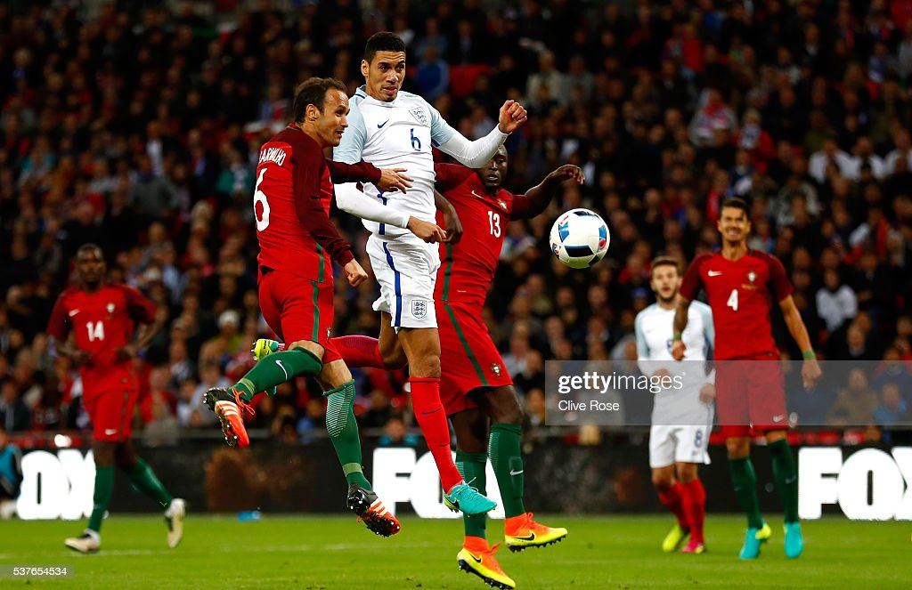 Chris Smalling of England beats Ricardo Carvalho and Danilo Pereira of Portugal as he scores their first goal during the international friendly match...