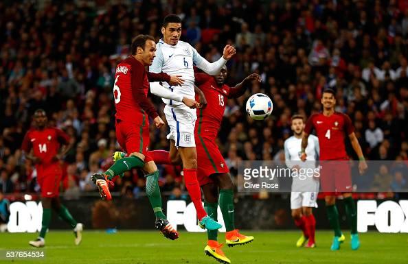 Chris Smalling of England beats Ricardo Carvalho and Danilo Pereira of Portugal as he scores their first goal during the international friendly match...