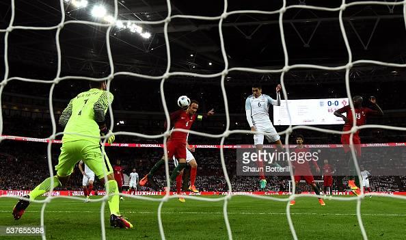 Chris Smalling of England beats Ricardo Carvalho and Danilo Pereira of Portugal as he scores their first goal past goalkeeper Rui Patricio of...