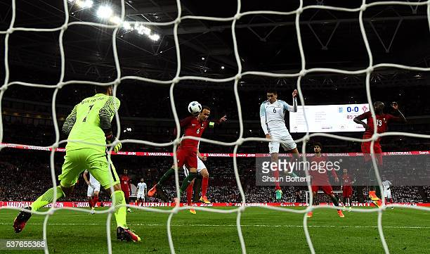Chris Smalling of England beats Ricardo Carvalho and Danilo Pereira of Portugal as he scores their first goal past goalkeeper Rui Patricio of...