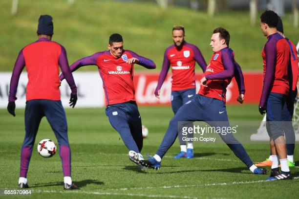 Chris Smalling of England tackles Phil Jones of England during an England training session at St Georges Park on March 21 2017 in BurtonuponTrent...