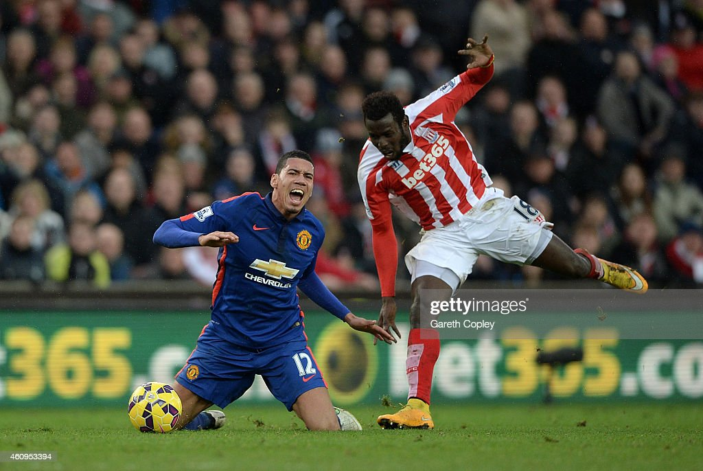 Chris Smalling of Manchester United competes with Mame Diouf of Stoke City during the Barclays Premier League match between Stoke City and Manchester United at Britannia Stadium on January 1, 2015 in Stoke on Trent, England.