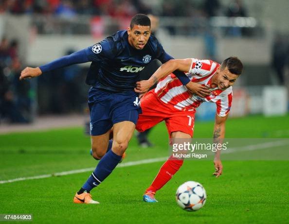 Chris Smalling of Manchester United holds off the challenge of Hernan Perez of Olympiacos during the UEFA Champions League Round of 16 first leg...